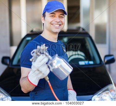 Car body repairer holding a spray gun