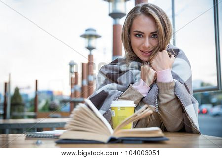 Portrait of a happy female student sitting with book and coffee in cafe