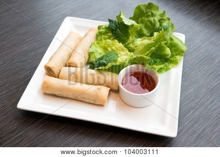 Fried spring rolls served with salad and sauce