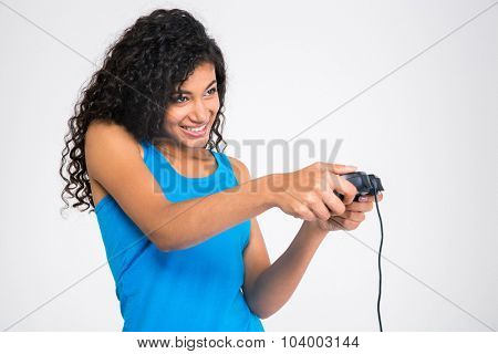 Portrait of a cheerful afro american woman playing in video game with joystick isolated on a white background
