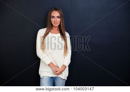 Portrait of a happy beautiful girl standing over gray background and looking at camera