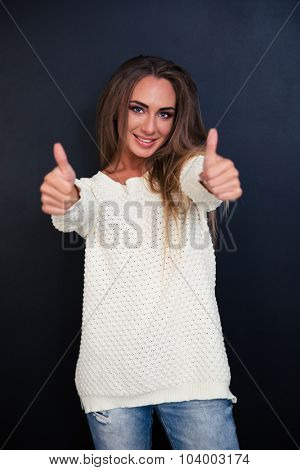 Portrait of a smiling pretty girl showing thumbs up over gray background and looking at camera