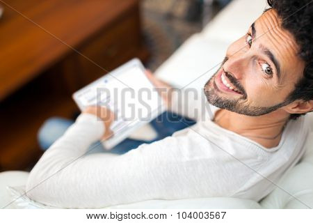 Man using a tablet while relaxing on the couch