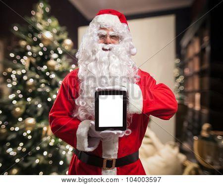 Portrait of Santa Claus holding a tablet computer