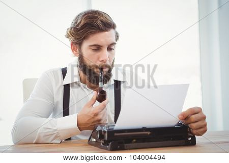 Hipster with smoking pipe working on typewriter at desk in office