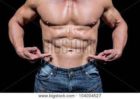 Midsection of shirtless man pointing at abs against black background