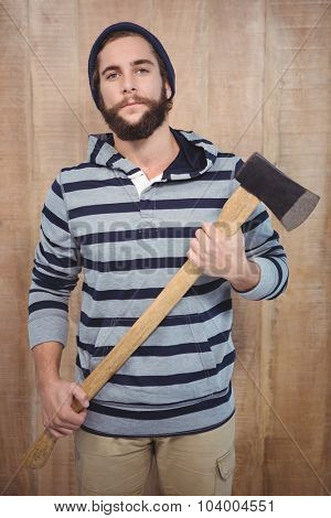 Portrait of confident hipster with hooded shirt holding axe against wooden wall