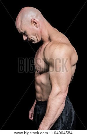 Side view of sad muscular man looking down against black background