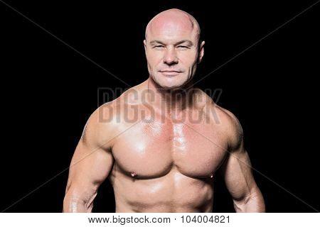 Portrait of confident muscular man against black background