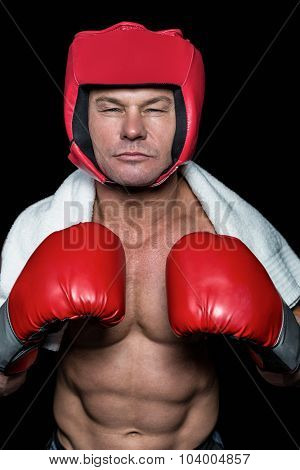 Confident boxer with gloves and headgear against black background
