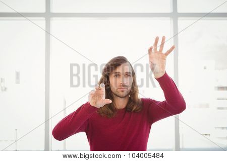 Creative businessman gesturing while standing against window in office
