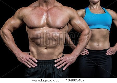 Midsection of muscular man and woman standing with hands on hip against black background