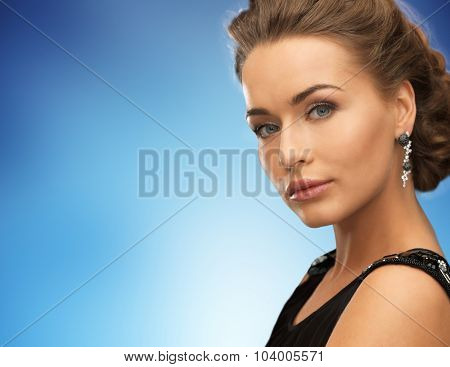 people, holidays and glamour concept - beautiful woman wearing earrings over blue background