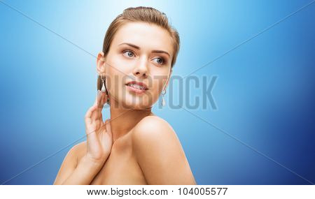 beauty, luxury, people, holidays and jewelry concept - beautiful woman with diamond earrings over blue background