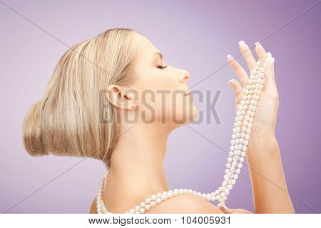 beauty, luxury, people, advertisement and jewelry concept - beautiful woman with sea pearl necklace or beads in hand over violet background