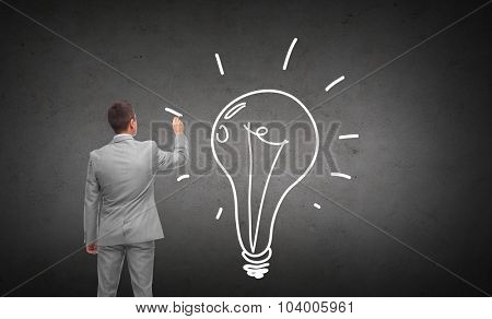 business, people, advertisement , information and office concept - businessman drawing lighting bulb from back over dark gray concrete wall background