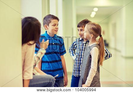 education, elementary school, children, break and people concept - group of smiling school kids talking in corridor