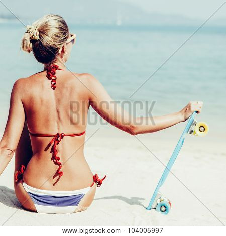 Sexy Suntanned Lady With The Blue Penny Board Rests On The Beach