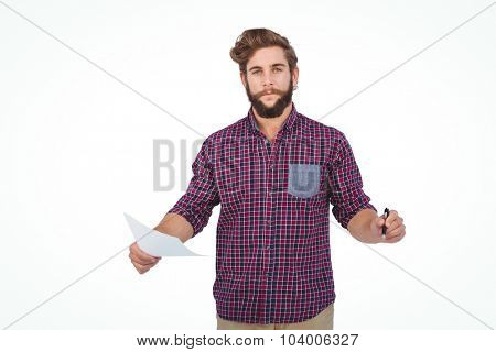 Portrait of confident hipster holding pen and paper standing against white backgroiund