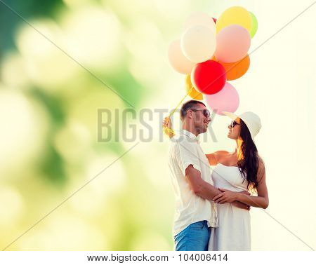 love, wedding, summer, dating and people concept - smiling couple wearing sunglasses with balloons hugging over green background