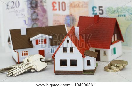 Model houses and keys with British Pounds in the background