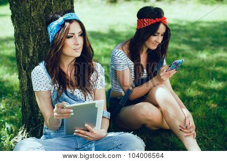 Young brunette twins girls sitting in the park. One girl with tablet looking to the side. Second girl chatting and social networking on mobile phone. Wearing denim jumpsuit and color bandanas.