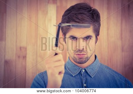 Portrait of serious hipster holding straight edge razor against wooden wall