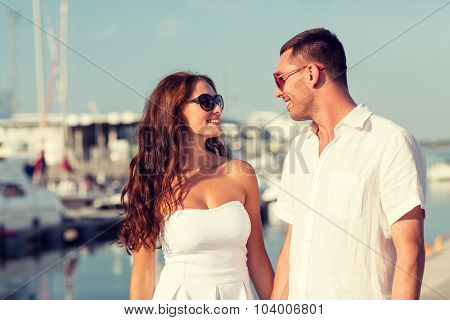 love, travel, tourism, sailing, people and friendship concept - smiling couple wearing sunglasses walking at harbor