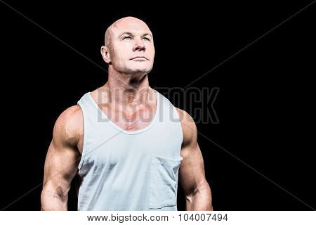 Bodybuilder in vest looking up against black background