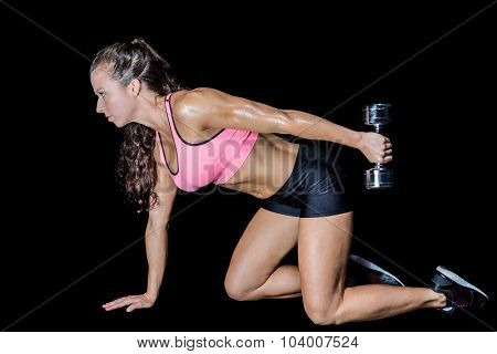 Side view of woman kneeling while lifting dumbbell against black background