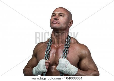 Confident bodybuilder holding chain while looking up against white background