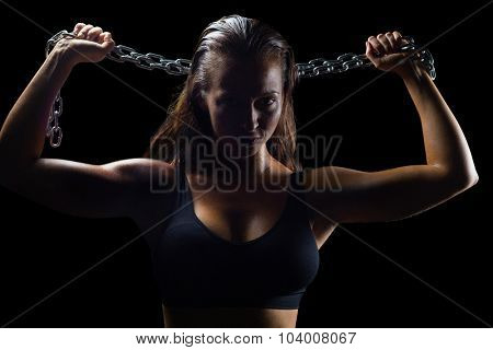 Portrait of athlete in sportswear holding chain against black background