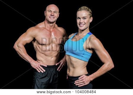 Portrait of happy man and woman with hand on hip against black background
