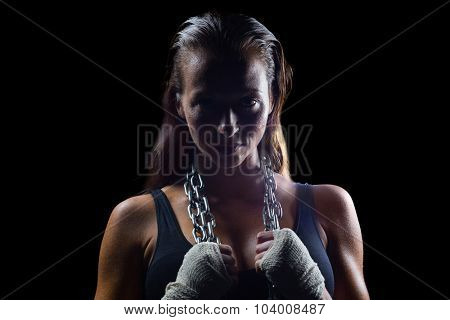 Portrait of female boxer holding chain around neck against black background