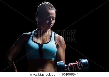 Fit woman concentrating while lifting dumbbell against black background