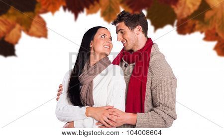 Young couple smiling and hugging against autumn leaves pattern