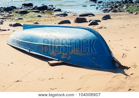 Old Blue Rowboat Lays On Sandy Beach