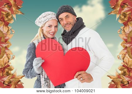 Portrait of happy couple holding heart against blue sky