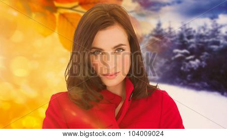 Portrait of a beautiful brunette in red coat against autumn changing to winter