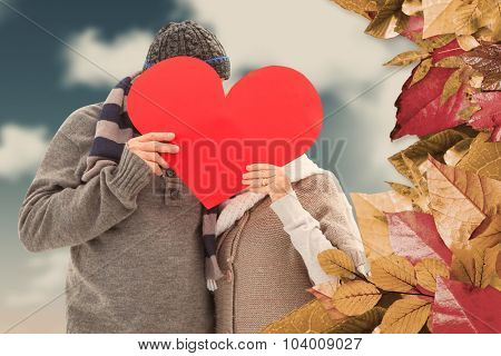 Happy mature couple in winter clothes holding red heart against blue sky