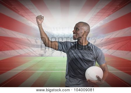 Sportsman with clenched fist holding rugby ball after victory against linear design