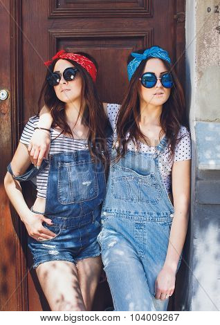 Attractive young brunette twins girls in stylish sunglasses hugging. Wearing denim overalls bright bandanas posing in front of old doors. Outdoors. Summer day.