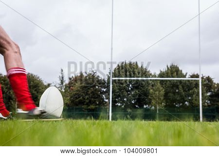 Rugby player kicking the ball at the park