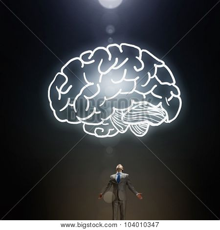 Businessman with hands spread wide and human brain above his head