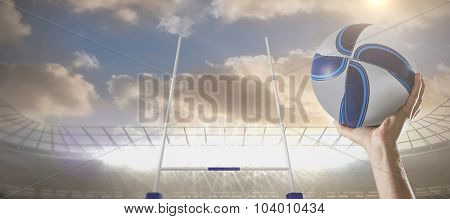 Rugby player with arm raised holding ball against rugby stadium