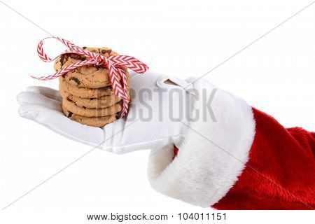 Closeup up of Santa's white gloved hand holding Chocolate Chip cookies ties with festive holiday ribbon. Horizontal format over white.