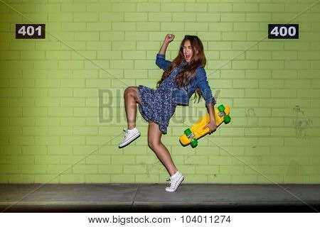 Beautiful Long-haired Girl With A Color Penny Shortboard Near A Green Brick Wall