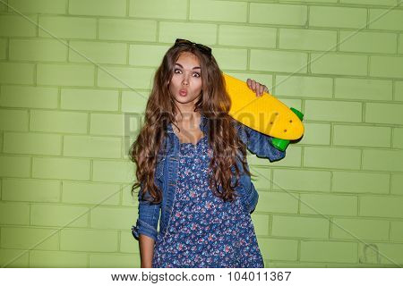 Beautiful Long-haired Lady With A Color Penny Shortboard Near A Green Brick Wall