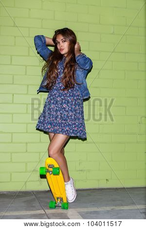 Beautiful Long-haired Woman With A Yellow Penny Skateboard Near A Green Brick Wall