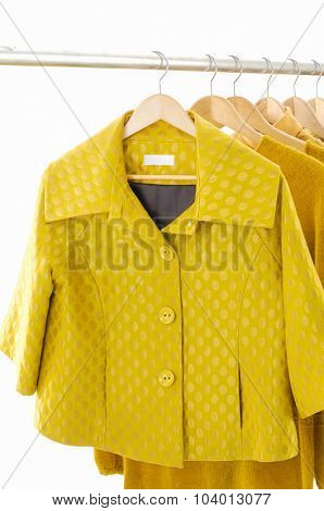 Set of female yellow dress with coat isolated on hanging